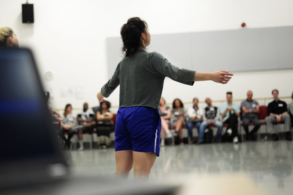 A dancer performs in a dance studio in front of invited guests at Phoenix Dance Theatre's CC Labs 2019. Her back is to the camera and she spreads her arms out side to side. Her dark hair is tied up and she wears a dark green top with blue shorts.