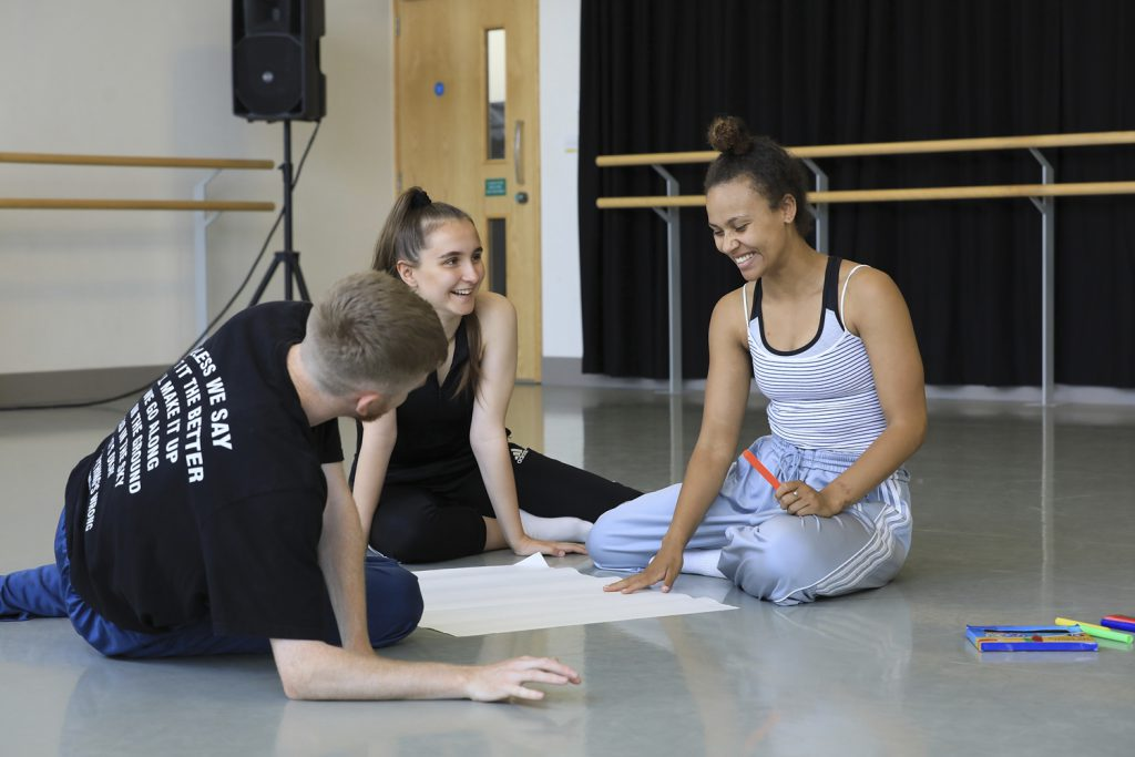 Three dance artists sit on the floor of a studio around a large white piece of paper. One of them is holding an orange pen and is laughing, one is smiling and the other has their back to the camera. They are all dance artists on Northern Ballet's Springboard course.