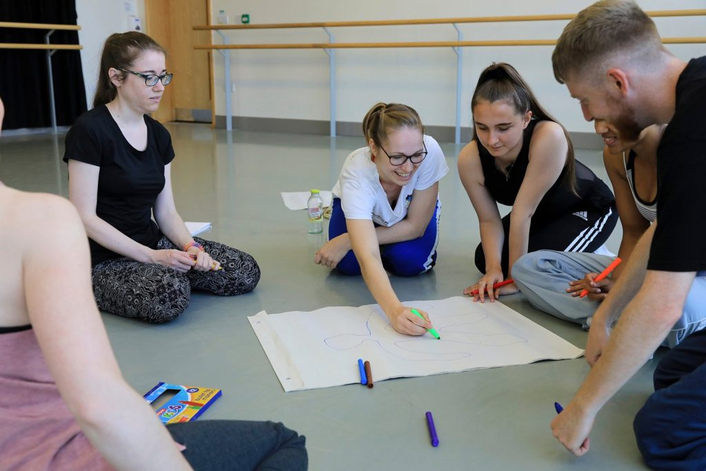 Five early career dance artists sit around a big white sheet of paper with the outline of a person drawn on it in blue. One of the dance artists is holding a bright green pen and is about to make some notes on the paper. The dance artists are smiling and are sat around the paper on the floor of a dance studio. This is part of Northern Ballet's Springboard Course.