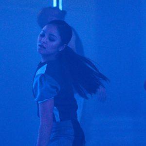 A dancer in Strange Stranger, the image is very blue.