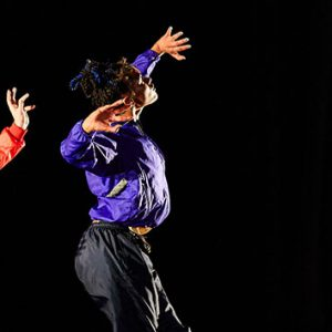 Three dancers performing as part of the Artist Fellowships sharing. They are wearing bright coloured tracksuit tops - one purple, one red and one green.