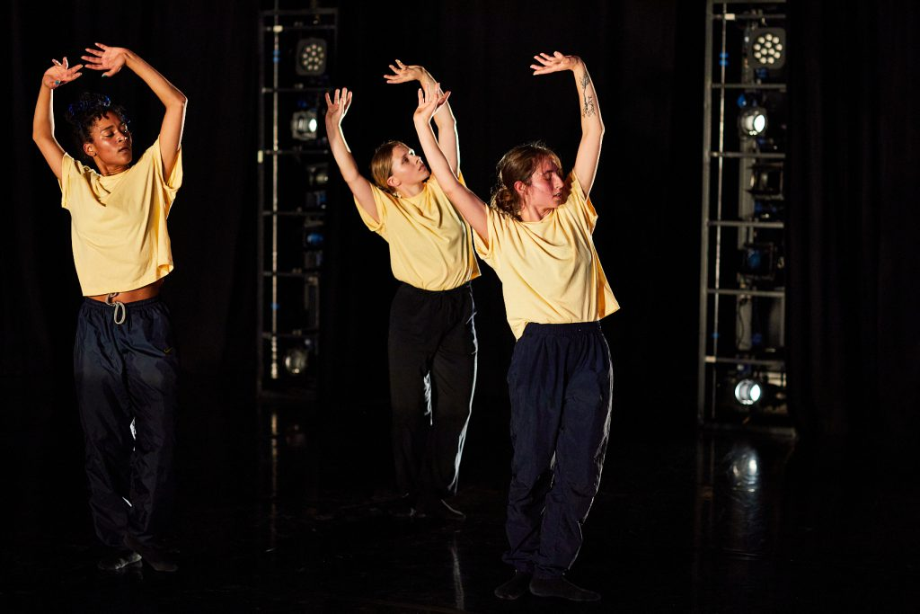 Three dancers wearing yellow t-shirts hold their hands above their heads as they perform as part of the Leeds Dance Partnership Artist Sharing