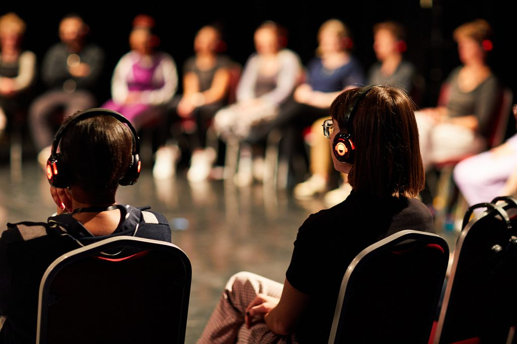 A group of people sit ina  circle with headphones on during Hannah Buckley's presentation at the Leeds Dance Partnership Artist Fellowships sharing.