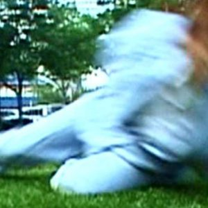 A blurred image of a dancer on the grass. The dancer is wearing pale blue.