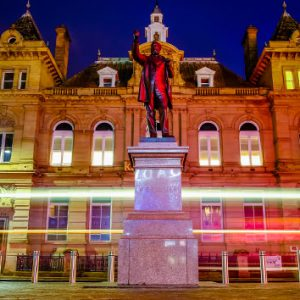 The Kala Sangam building in Bradford. it is nighttime and a statue of a man is front and centre in front of the building.