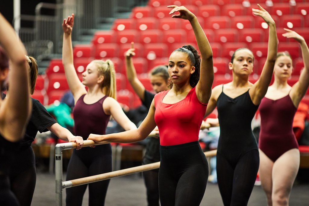 A group of dance students stand at the barre in the Ballet Black workshop. They have one hand on the barre, with the other arm in the air above thier heads.