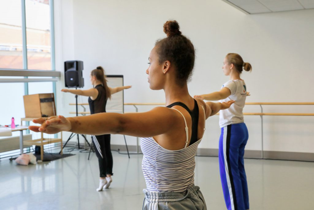 A dancer stands with their arms outstereched left and right. Thery are in half-profile to the camera. They are in a dance studio.