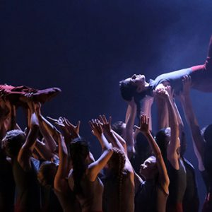A contemporary dance performance. A group of dancers stand together, holding two dancers horizontally above their heads. One of the dancers has their right leg in the air, the other is laid like a pencil, arms stuck to their sides and legs together.