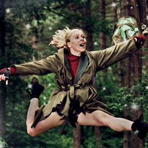 A dancer is leaping in the air. She is dressed as Jub, a character from The Lost Happy Endings.. She is wearing a green jacket, and is holding onto a magical quill and bag. She is in a forest.