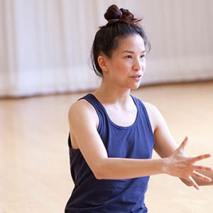 A dance artist sits on the floor of a studio. She is speaking to a group of people, her hands are outstretched.