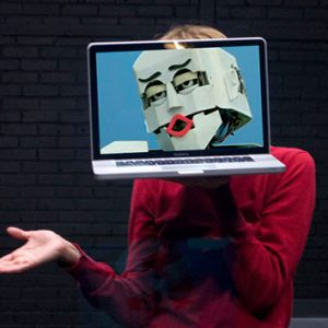 A woman is holding a laptop in front of her face. The laptop screen is displaying a cartoon-ish face.