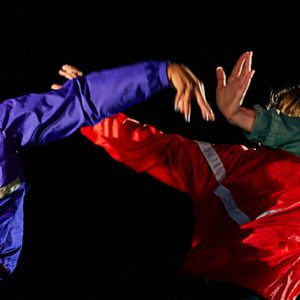 Three dancers wearing bright sports jackets. They have their backs to the camera and have their arms outstretched.