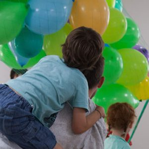 Two adult dancers and a child are featured. One of the adult dancers, wearing a yellow tshirt, is gesturing to some balloons. The other is giving the child a piggy back.