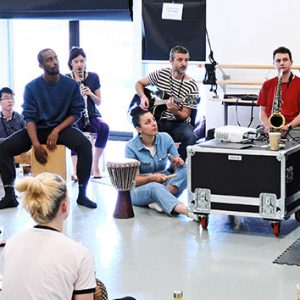 A group of people sit on the floor of a studio. They are sat in a semi-circle. There is also a harp player.