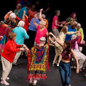 A group of people are dancing together, the camera looking down on them from height. Many of them are wearing bright coloured clothing. They are in a dance studio with black floors and walls.
