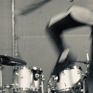 A person is jumping in front of a drum. The image is black and white.