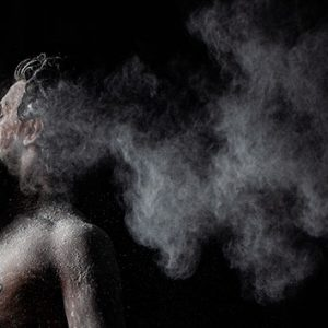 Two dancers in a promotional image for Seeta Patel's Rite of Spring. One is in profile to the camera, the other stands in front of them, looking backwards. They both have white powder covering them, and a smoke of white powder trailing behind them.