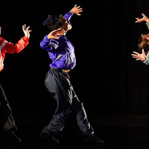 Three dancers perform, they are each wearing a zip up tracksuit top - one in red, one in blue and the last one in green.