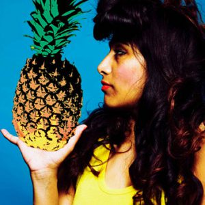 A woman stands in profile to the camera. She is holding a pineapple in her hand.