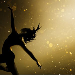 A silhouette of a dancer striking a pose in front of a golden and black sparkly background.