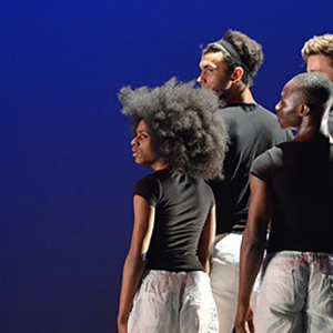 A group of four dancers stand in a tight diagonal square on the right as we look at the image. They have their backs to the camera and are all facing to the left. They are wearing black t-shirts and white trousers.
