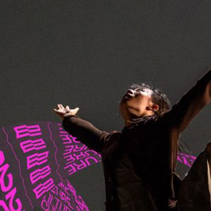 A dancer holds their arms out in the air in a wide v shape and look up. The words LEEDS 2023 YEAR OF CULTURE are written several times in a purple/pink font that runs in waves throughout the image.